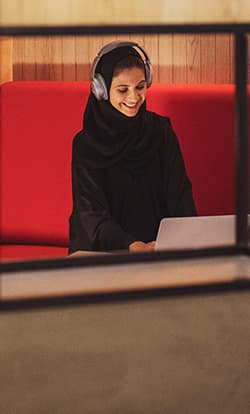 A woman with headphones happily working at one of our office spaces in Dubai Production City